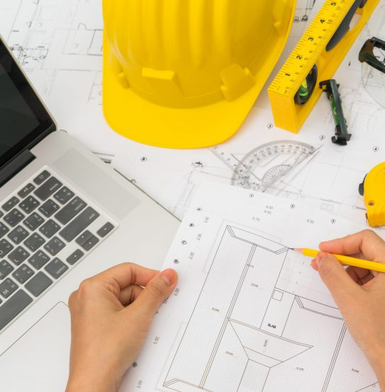 Hand over Construction plans with yellow helmet and drawing tool